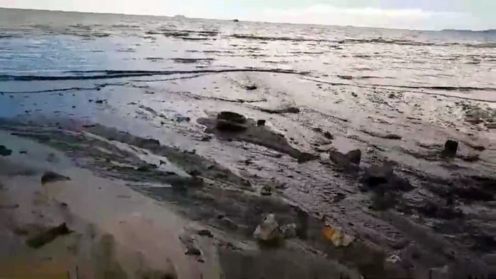 The ugly mass of raw sewage covers the beach.