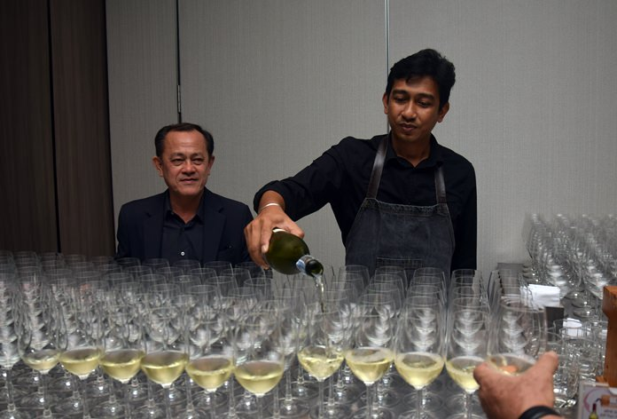 Teera Weerawan keeps watch as a waiter pours wine with poise and style.