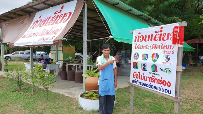 Kon Sihong points to the humorous sign in front of his 'Chicken & Gourd Phit(sanu)lok Noodles' shop.