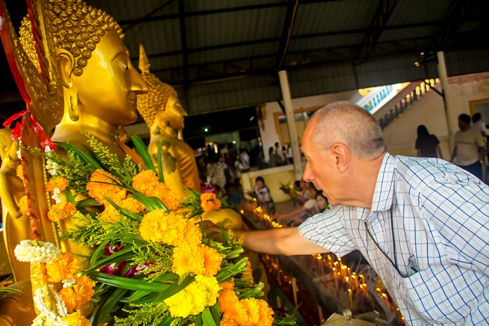 A foreign resident pays his respects to Lord Buddha.