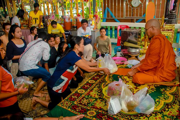 Locals present their 'Sangkatan' offerings of food and necessary items to a Buddhist monk.