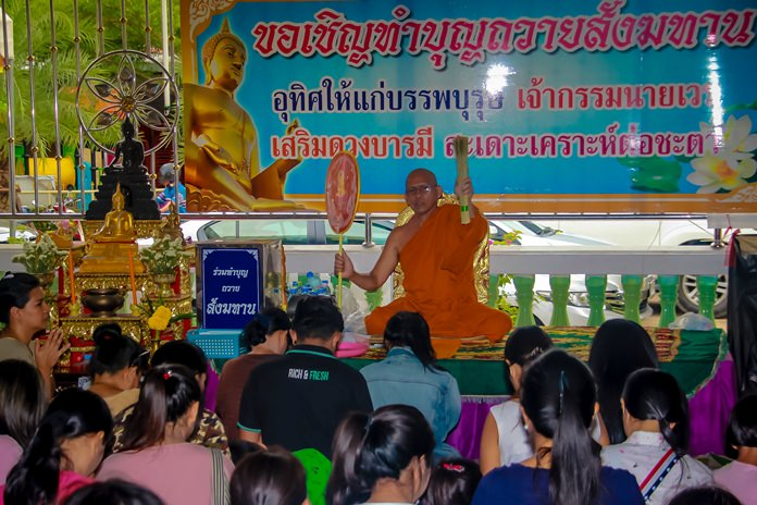 A Buddhist monk sprinkles holy water on the faithful at Wat Suthawat in Nongprue.