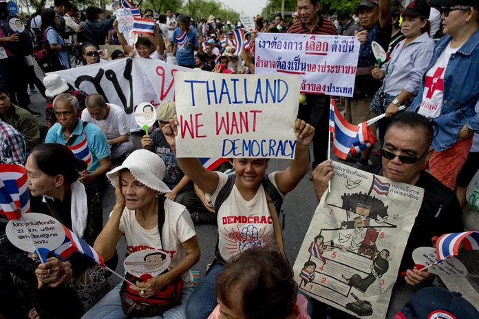 Pro-democracy supporters stage a sit-in protest in front of a police line during a gathering to mark the fourth anniversary of the military take-over of government in Bangkok, Tuesday, May 22. (AP Photo/Gemunu Amarasinghe)