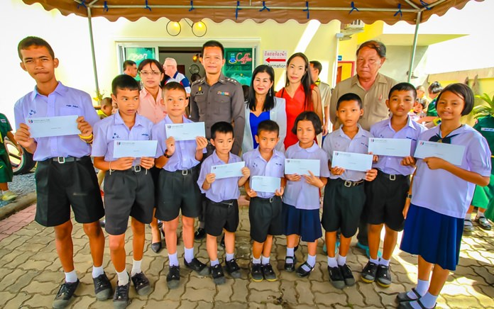Pol. Capt. Yongyuth Kongthong, Sub-Inspector at Huay Yai Police Station, and PSC Social Welfare Chairwoman Noi Emerson (both standing, center) pose with some of the scholarship recipients.
