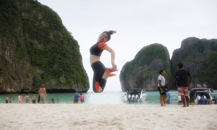 A tourist jumps for a photo on the popular beach at Maya Bay on Koh Phi Phi Leh.