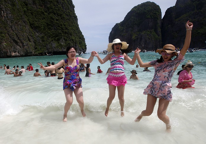 Tourists jump in the waves in Maya Bay.