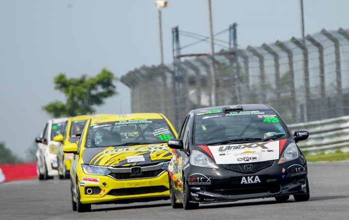 Victor Jensen steers his Honda Jazz (right) down the straight in the Super Production Class.