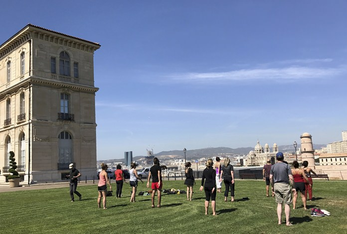 Guests from a Regent Seven Seas cruise perform tai chi outdoors on a port call in Marseille, France, with a view of the sea. (Harrison Liu via AP)