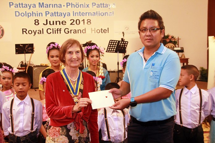 On behalf of the children from the CPDC, Siromes Akrapongpanich (right) receives a token of appreciation from President Margret Deter.