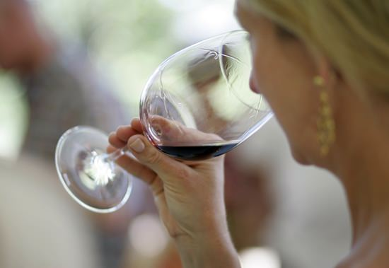 A woman evaluates the aroma of a wine in California. On Friday, June 15, 2018, National Institutes of Health Director Dr. Francis Collins announced the NIH is shutting down a study that was supposed to show if a single drink a day could prevent heart attacks, citing ethical problems that would undermine the credibility of its findings. (AP Photo/Eric Risberg, File)