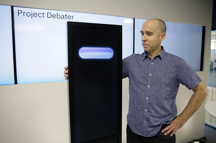 Dr. Noam Slonim, principal investigator, stands with the IBM Project Debater before a debate between the computer and two human debaters Monday, June 18, 2018, in San Francisco. The system, called Project Debater, is designed to be able to listen to an argument, then respond in a natural-sounding way, after pulling in evidence it collects from Wikipedia, journals, newspapers and other sources to make its point. (AP Photo/Eric Risberg)