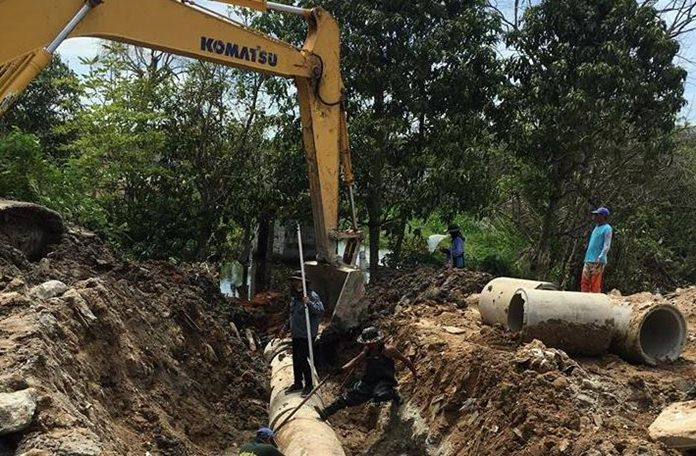 City workers install 60 centimeter tunnels to prevent floods near Pattaya Floating Market.