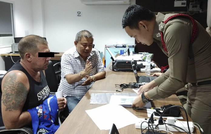 Australian Stephen Allan Carpenter, left, is detained by police in Pattaya, Thailand. Carpenter was arrested on vice charges in a sting operation after allegedly offering a sex cruise with prostitutes via a Facebook page. (AP Photo)