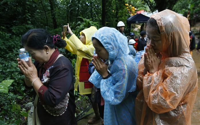 Relatives of 12 young soccer team members and their coach pray for their rescue, Wednesday, June 27, in Mae Sai, Chiang Rai province. (AP Photo/Sakchai Lalit)