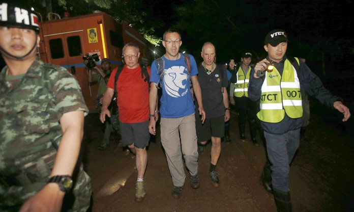 The British Cave Rescue Council members from second left, Robert Charles Harper, John Volanthen and Richard William arrive at cave in the staging area as they continue the search for a young soccer team and their coach believed to be missing in a large cave, Wednesday, June 27, 2018, in Mae Sai, Chiang Rai province, in northern Thailand. (AP Photo/Sakchai Lalit)