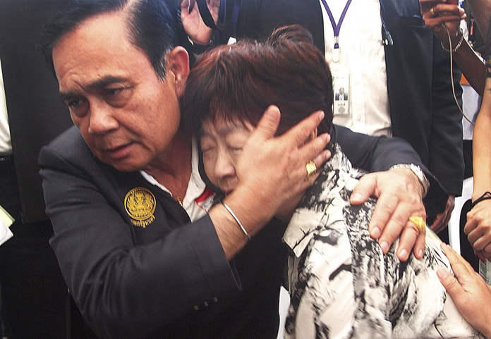 Thailand Prime Minister Prayuth Chan-ocha consoles a relative of a victim of last week's boat accident, Monday, July 9, on Phuket island. (AP Photo)