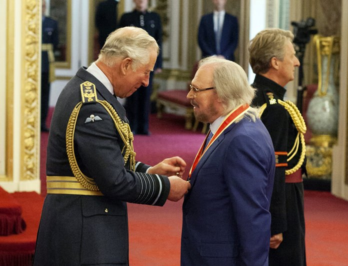 Singer and songwriter Barry Gibb talks with Prince Charlesm (left) during an Investiture ceremony to award a knighthood to Gibb, at Buckingham Palace in London, Tuesday June 26. (Dominic Lipinski/PA via AP)