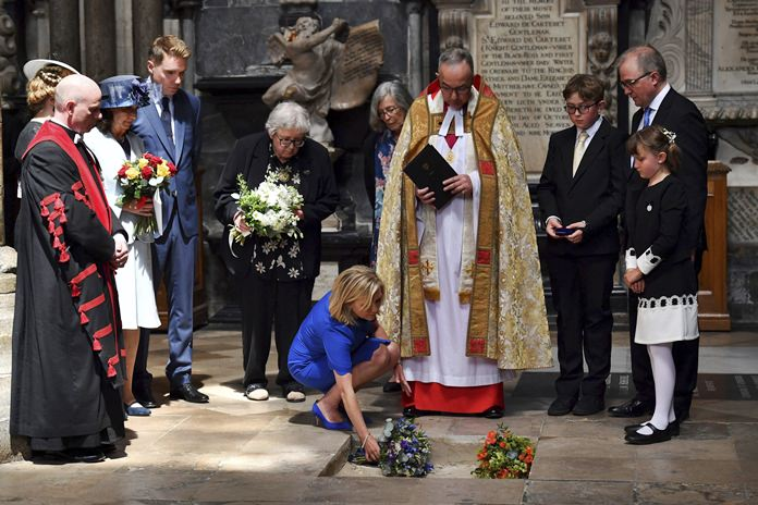 Lucy Hawking lays flowers as the ashes of her father, Professor Stephen Hawking, are laid to rest during his memorial service at Westminster Abbey in London, Friday June 15, 2018. Hawking has taken his place among Britain's greatest scientists with his ashes buried in Westminster Abbey, between the graves of Charles Darwin and Isaac Newton. (Ben Stansall/PA via AP)