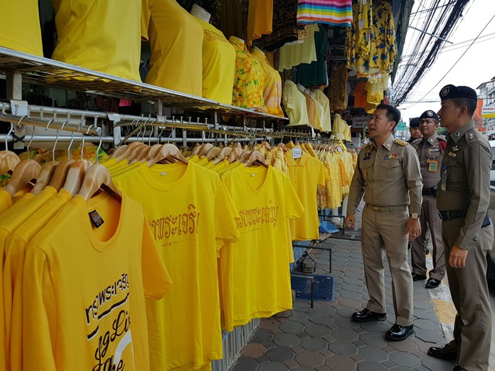 District Chief Naris Niramaiwong leads a check of clothes stores to make sure yellow shirts sold this month for HM the King's birthday meet proper standards.