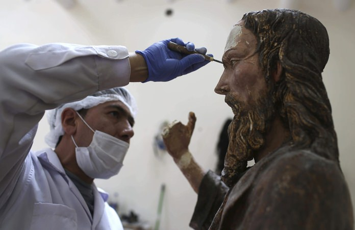 An art restorer works on a sculpture of Jesus Christ in a studio of the Ministry of Culture's Restoration Center in Cuzco, Peru. (AP Photo/Martin Mejia)