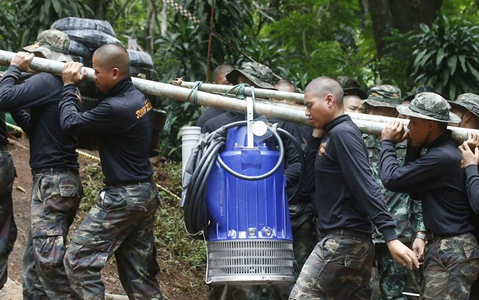 Soldiers carry a pump to help drain the rising flood water in a cave where 12 boys and their soccer coach were trapped since June 23. (AP Photo/Sakchai Lalit)