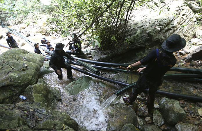 Thai soldiers drag pipes to divert mountain runoff water away from the cave where 12 boys and their soccer coach were trapped since June 23. (AP Photo/Sakchai Lalit)