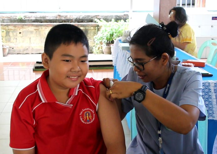 A brave student from Pattaya School No. 3 takes his diphtheria and tetanus vaccination shots with a smile.