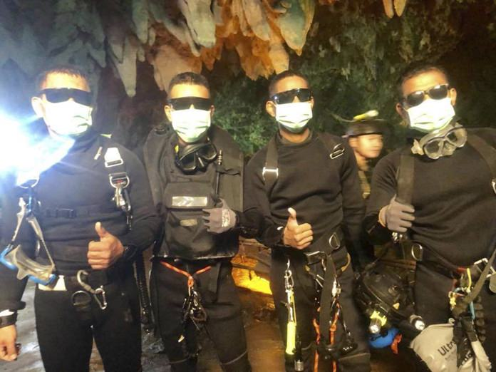 The last four Thai Navy SEALs give their thumbs up as they emerge safely after completing the rescued mission inside a cave where 12 boys and their soccer coach had been trapped since June 23, in Mae Sai, Chiang Rai, northern Thailand. Thailand's navy SEALs say all 12 boys and their soccer coach have been rescued, ending an ordeal that gripped the world as it lasted more than two weeks. (Royal Thai Navy via AP)