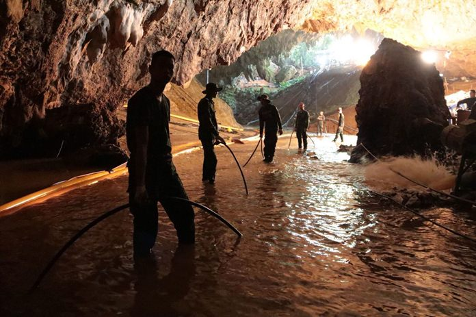 Thai rescue teams arrange the water pumping system at the entrance to the flooded cave complex on 7 July. (Royal Thai Navy via AP)
