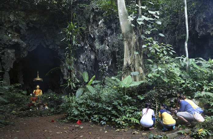 Family members pray in front of a Buddhist statue near the cave July 7, where 12 boys and their soccer coach have been trapped since June 23. (AP Photo/Sakchai Lalit)