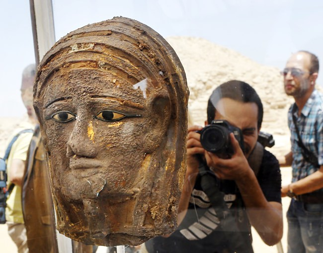 A photographer films a gilded silver mummy mask found on the face of the mummy of the second priest of Mut, as it is displayed during a press conference in front of the step pyramid of Saqqara, in Giza, Saturday, July 14, 2018. Archaeologists say they have discovered a mummification workshop dating back some 2,500 years at an ancient necropolis near Egypt's famed pyramids. (AP Photo/Amr Nabil)