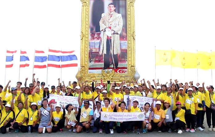 Runners and walkers pose in front of a photo of His Majesty the King on Pattaya Beach Road, Saturday, July 14, after completing a charity walk-run for the family of Navy SEAL Saman Kunan