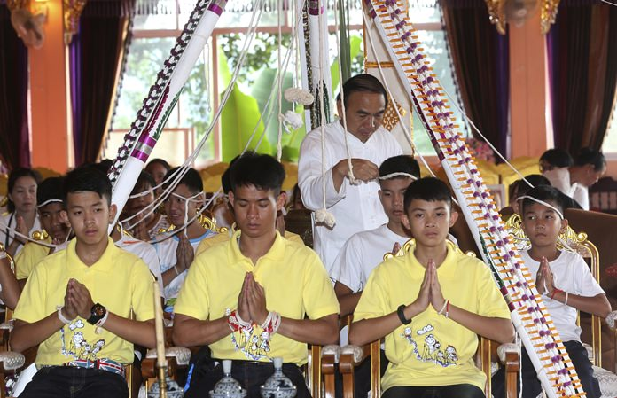 Soccer coach Ekkapol Janthawong, second from left, and members of the rescued soccer team attend a Buddhist ceremony in Mae Sai district, Chiang Rai province, Thursday, July 19. (AP Photo/Sakchai Lalit)