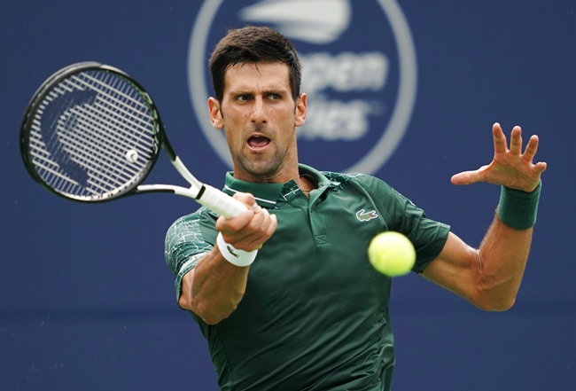 Novak Djokovic, of Serbia, returns a shot to Peter Polansky, of Canada, during the Rogers Cup men's tennis tournament in Toronto, Wednesday, Aug. 8. (Mark Blinch/The Canadian Press via AP)