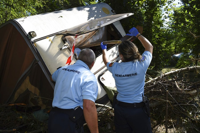 French gendarmes inspect a damaged trailer after floods in a camping site of Saint-Julien de Peyrolas, southern France, Friday, Aug. 10. (Jose Roca/French Gendarmerie National via AP)