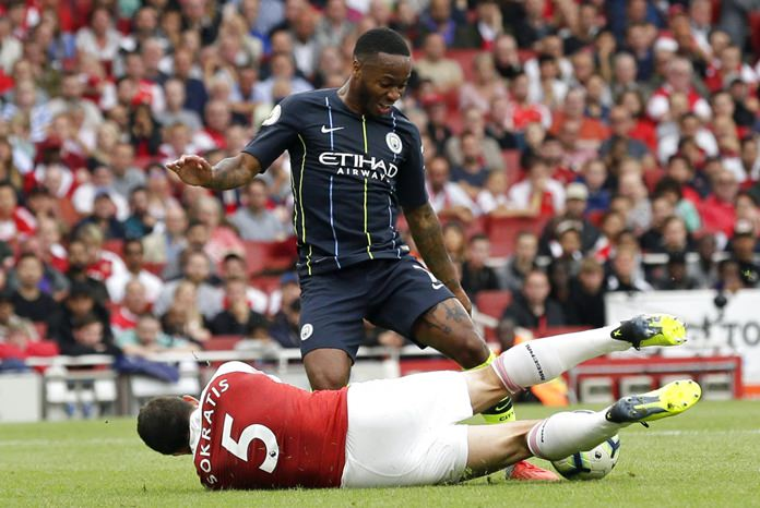 Arsenal's Sokratis Papastathopoulos falls down in front of Manchester City's Raheem Sterling during the English Premier League match between Arsenal and Manchester City at the Emirates stadium in London, Sunday, Aug. 12. (AP Photo/Tim Ireland)