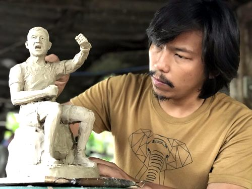 Artist Krisana Napulphol holds a sculpture of former Thai Navy SEAL Saman Kunan at his studio in Nakhon Pathom.