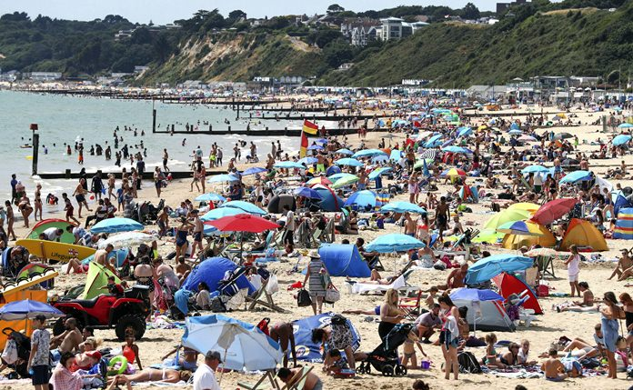 People enjoy the Bournemouth beach in Dorset, England, as the hot weather continues across Britain. (Andrew Matthews/PA via AP)
