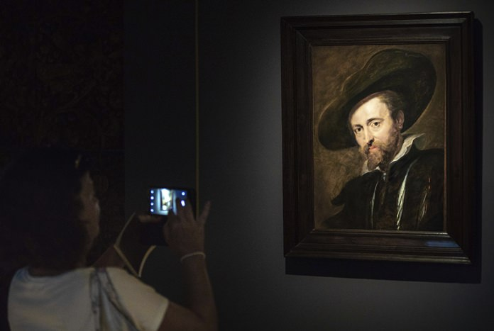 In this photo taken on Thursday, July 26, 2018, a visitor looks at the restored Peter Paul Rubens self-portrait from 1628 in the Rubenshouse in Antwerp, Belgium. (AP Photo/Olivier Matthys)
