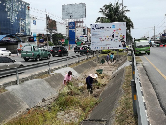 A work crew on Aug. 1 scooped out garbage blocking sewers, sucked out pipes and repaired broken grates in the Sukhumvit median near North Road. They also cut back grass blocking water flow.