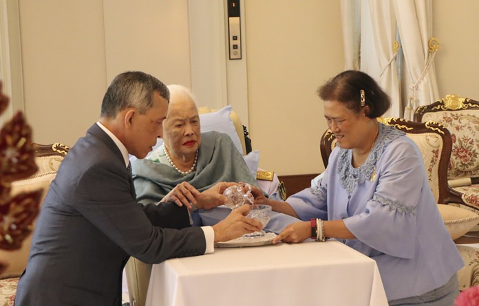 Her Majesty Queen Sirikit together with HM King Maha Vajiralongkorn and HRH Princess Maha Chakri Sirindhorn make merit by pouring holy water into a bowl. (The Royal Household Bureau via AP)