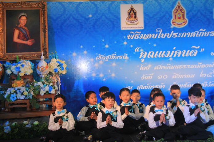 """A portrait of HM Queen Sirikit of the Ninth Reign looks over their shoulders as students from Pattaya City Schools sing """"Value of Mother's milk"""" and """"Im Oun"""" at Central Festival Pattaya Beach."""