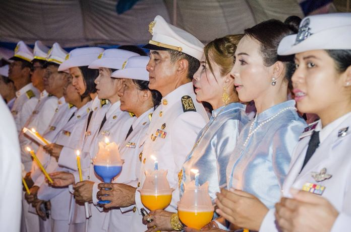 Public officials take part in a candlelight ceremony and sing songs for the Queen in front of Banglamung District Office.