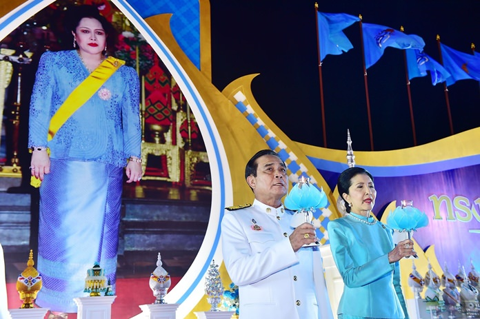 "Prime Minister Gen Prayut Chan-ocha and his wife Napaporn light ceremonial candles and sing the royal anthem at Sanam Luang August 12 before chanting ""Long Live the Queen"" three times. The PM led members of his Cabinet in giving alms to mark the birthday anniversary of Her Majesty Queen Sirikit of the Ninth Reign. (NNT Photo)"