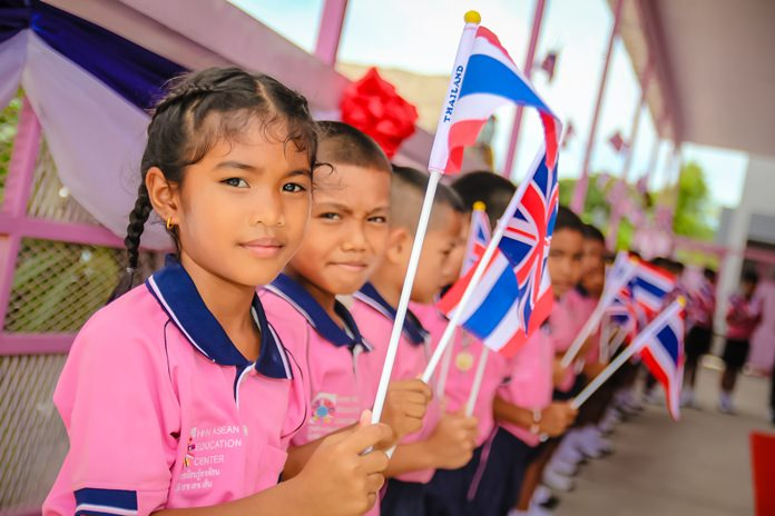Migrant children at the Drop-in ASEAN Education Center wave British and Thai flags to welcome H.E. British Ambassador Brian Davidson.
