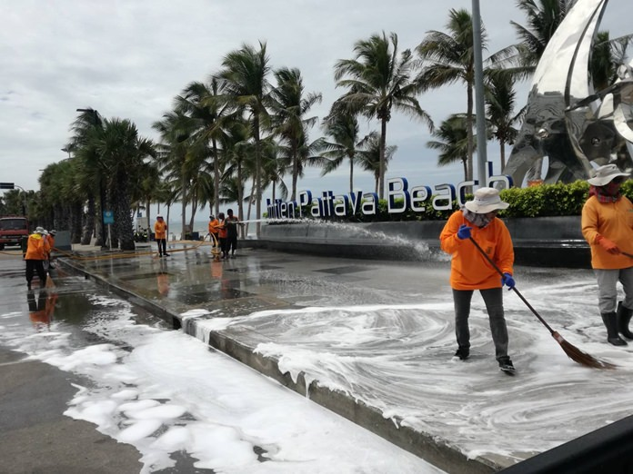 Pattaya sanitation workers clean up Jomtien Beach Road which stank of garbage-scented storm runoff.