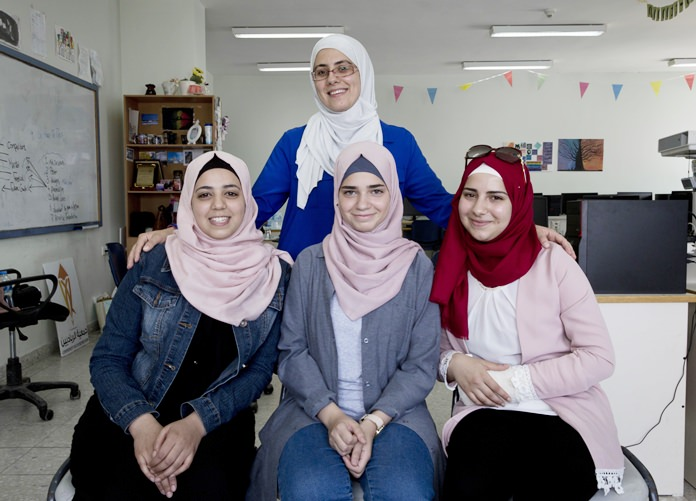 In this Thursday, Aug. 2, 2018 photo, Tamara Awaysa, 17, left, Wassan al-Sayyed, 17, center and Massa Halawa, 16, right, pose for a photo with their mentor Yamama Shakaa in the West Bank city of Nablus. The four Palestinian high school friends made it to the finals of a worldwide app competition among more than 19,000 teens. (AP Photo/Nasser Nasser)