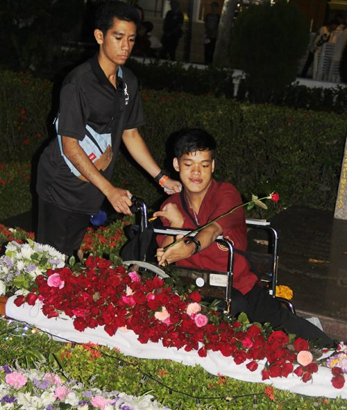 Hundreds of red roses were laid on Father Ray's grave.