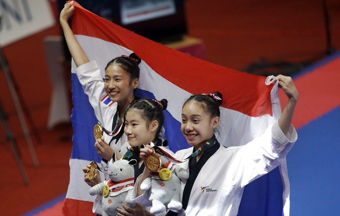 Thai athletes show their medals after winning gold in the Taekwondo women's team poomsae at the Asian Games in Jakarta, Sunday, Aug. 19. (AP Photo/Tatan Syuflana)