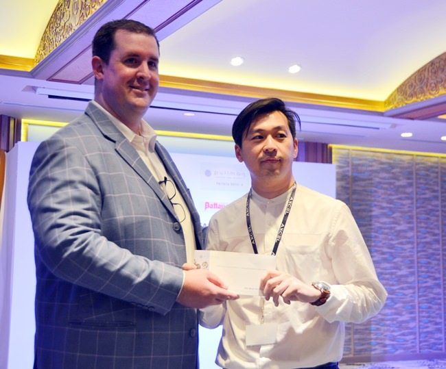 Simon Angove GM of the Pullman Pattaya Hotel G presents a draw prize to the lucky winner.
